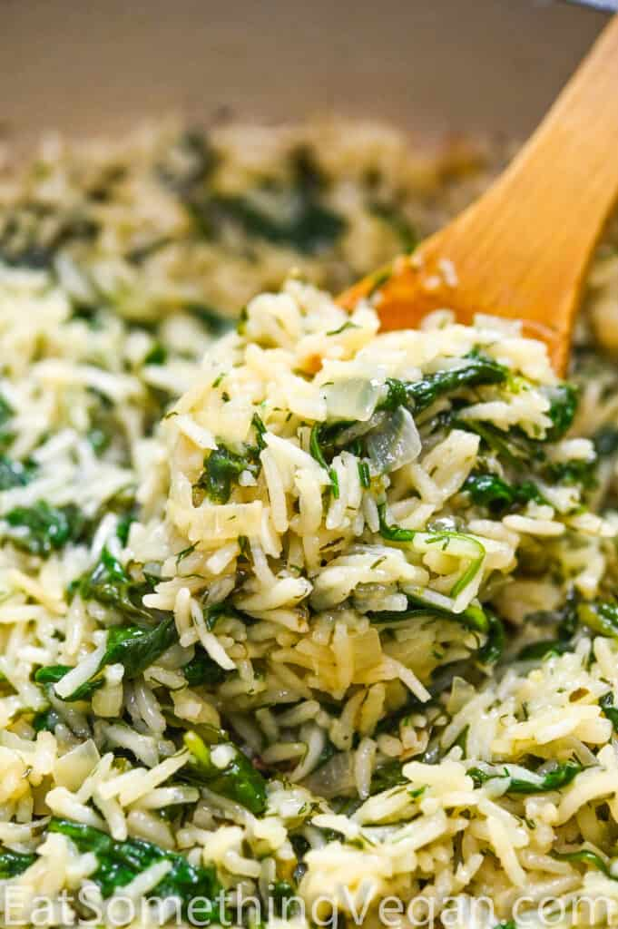 Spinach rice on a wooden spoon