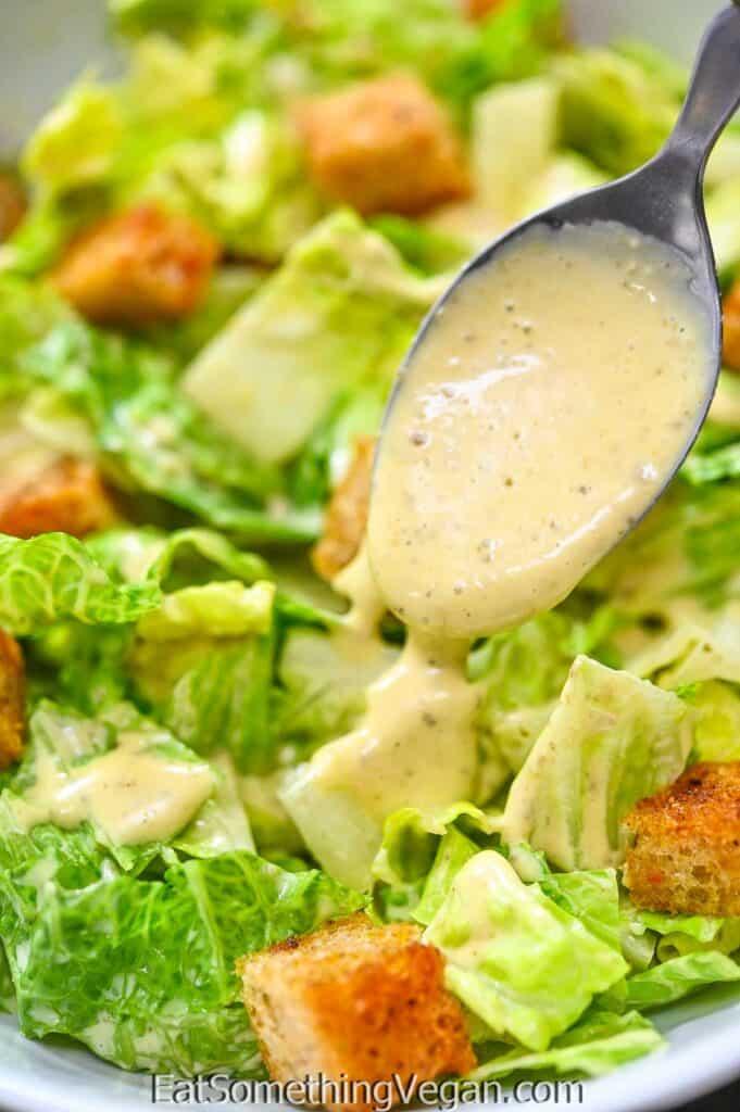 pouring Vegan Caesar Dressing over the lettuce
