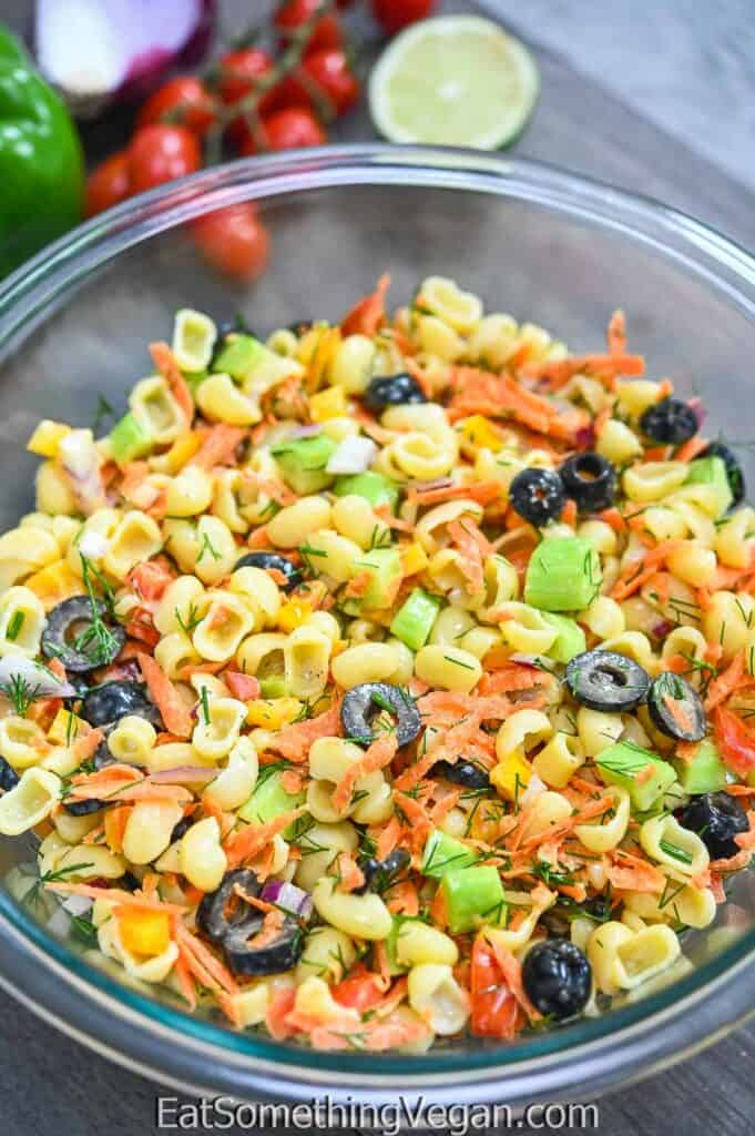 Vegan Pasta Salad in a bowl with veggies in the background