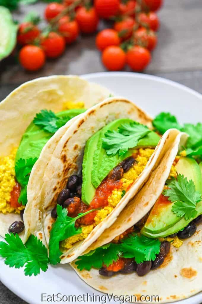 Vegan Breakfast Tacos on a plate with veggies in the background