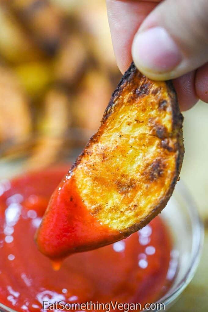 dipping Paprika Baked Potatoes in ketchup