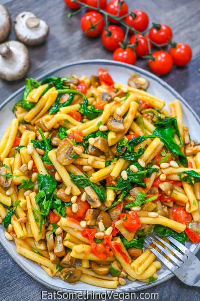 Tomato Mushroom Spinach Pasta on a plate with veggies on the background