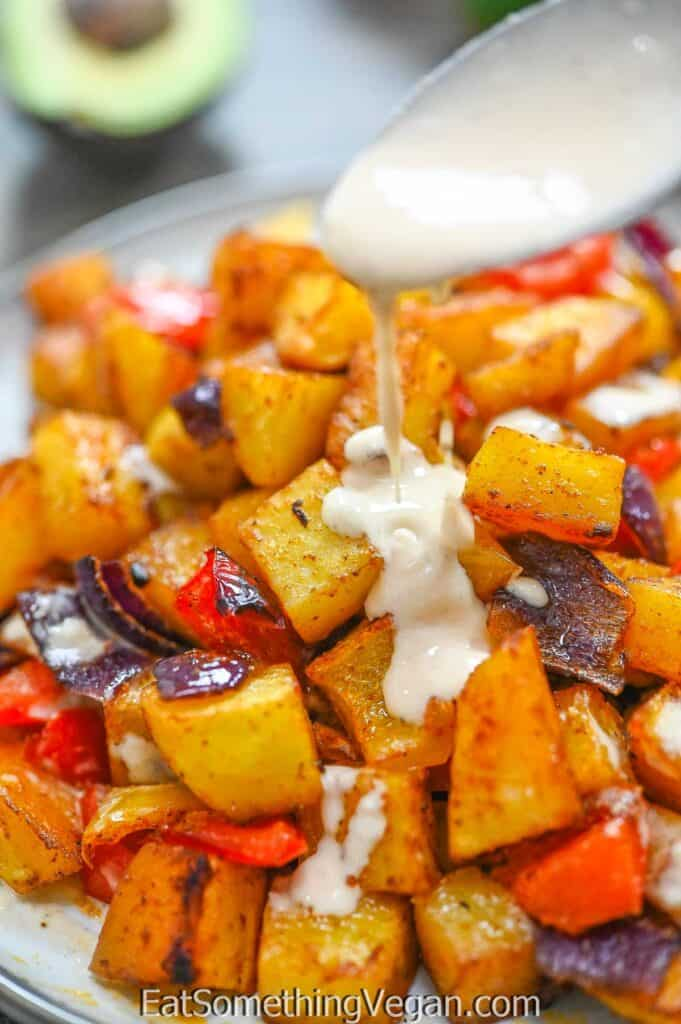 pouring tahini sauce onto Baked Potato Breakfast Hash