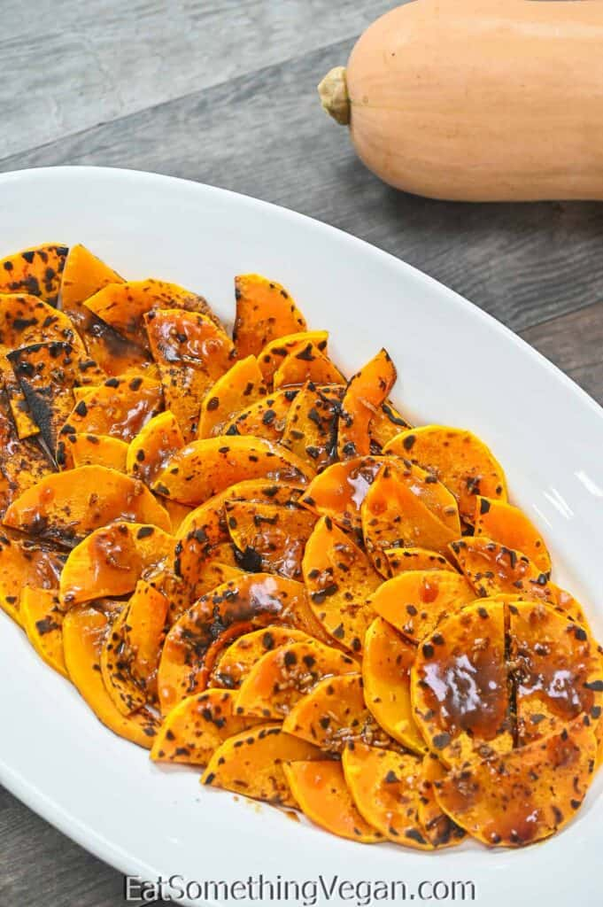 Roasted Pumpkin Salad on a plate with butternut squash on the background